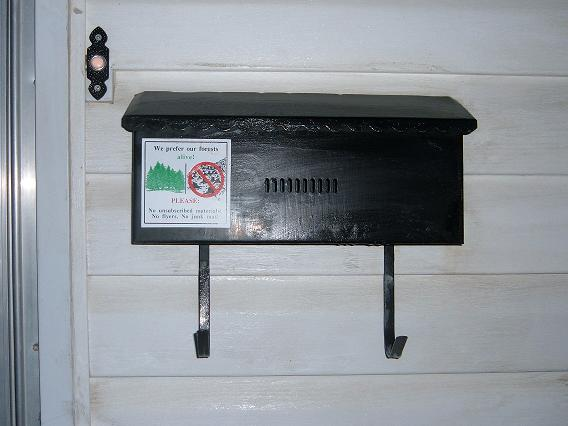 An attached or wall-mount letterbox, with a hook underneath for newspapers. Photo taken by Nellie Bly in Calgary, Alberta, Canada, on March 28, 2008.